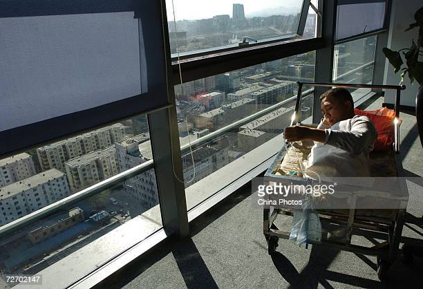 Peng Shuilin looks over a catheter December 2 2006 in Beijing China Peng Shuilin was hit by a freight truck in a traffic accident in 2004 and his...