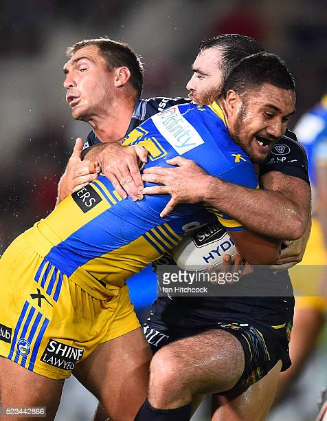 Peni Terepo of the Eels is tackled by Scott Bolton and Kane Linnett of the Cowboys during the round eight NRL match between the North Queensland...