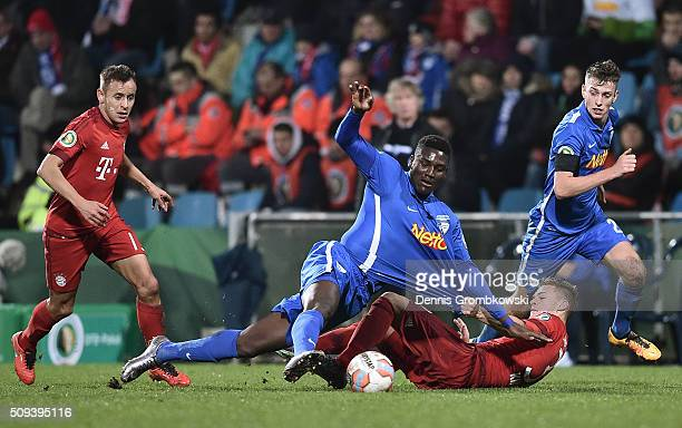 Peniel Kokou Mlapa of VfL Bochum is tackled by Joshua Kimmich of Bayern Muenchen during the DFB Cup quarter final match between VfL Bochum and Bayern...