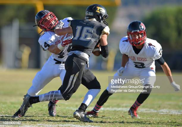 Peninsula's Andrew Phillips is stopped by PV's Lucas Cooper left and Austin Rule in Rolling Hills Estates CA on Friday November 07 2014