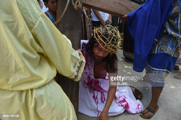 A penitent acting as Jesus reenacts the passion and death of Christ during the annual observance of Lent on Good Friday in Cainta town Rizal province...