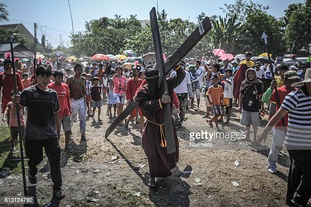 A penitent carries as wooden cross as he takes part in a reenactment of Jesus Christ's crucifixion during Good Friday in San Fernando town Pampanga...