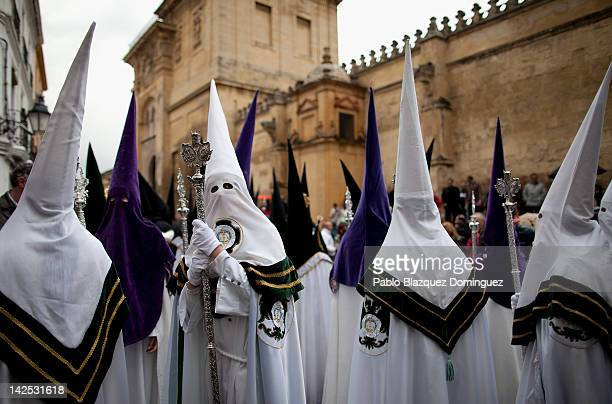 A penitent checks back at Nuestra Senora de los Dolores Coronada figure of the Dolores brotherhood during the Holy Week procession near the Cordoba...