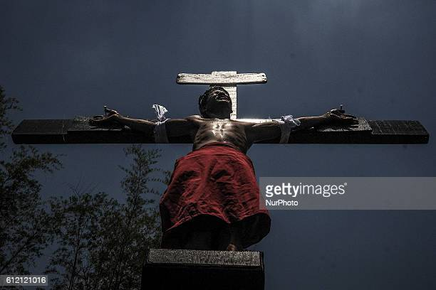 A penitent hangs from a wooden cross as he takes part in a reenactment of Jesus Christ's crucifixion during Good Friday in San Fernando town Pampanga...