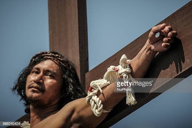 A penitent is nailed to a wooden cross as he takes part in a reenactment of Jesus Christ's crucifixion during Good Friday in San Fernando town...