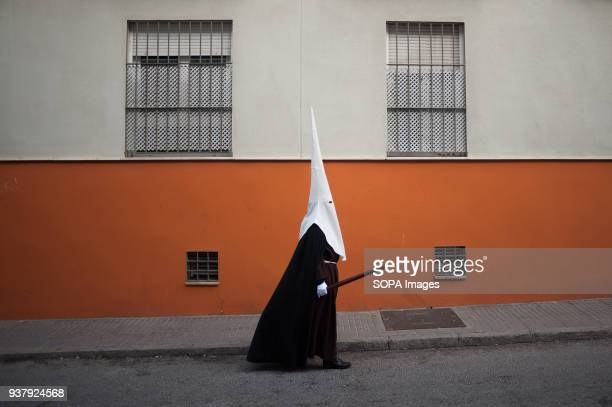 A penitent of 'Dulce Nombre' brotherhood walks along the street during the Holy Week in Malaga The Holy Week in Andalusia is one the most important...