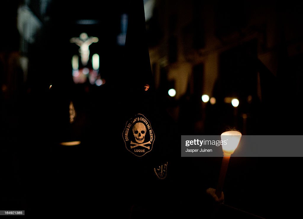 A penitent of the Cofradia del Santisimo Cristo del Silencio y la Expiracion brotherhood carries a candle while taking part in a holy week procession on March 29, 2013 in Luque near Cordoba, Spain. The origin of this small brotherhood, which uses a skull with crossed shins prominently as their symbol, referring to the mortality and short duration of life but also to the triumph of Jesus over death, dates back to the fifties when a group of young catholic's came up with the idea of forming the brotherhood. Since its founding the brotherhood has a strict penitential character with one of its aims being the public prayer of the Stations of the Cross in the early hours of Good Friday through the streets of this small Andalusian town. Home to the brotherhood is the San Nicolas de Tolentino convent church which was founded in 1626 and dedicated to Our Lady of Grace.