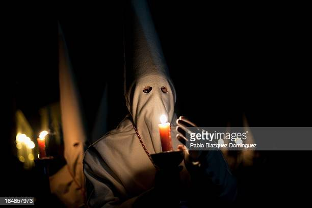 A penitent protects the flame of a candle during the Holy Week procession of the Cofradia Jesus Yacente on March 29 2013 in Zamora Spain Easter week...