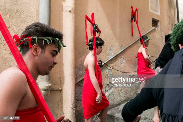 Penitents called Hecce Homo run together with a Vattiente during a procession on Holy Friday in Nocera Terinese in the Calabria region of southern...