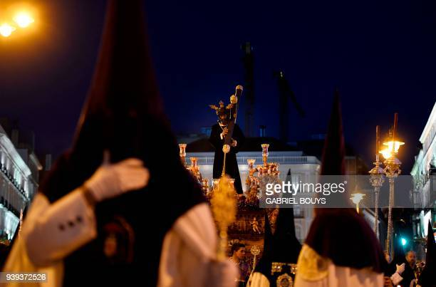 Penitents carry a figure of 'Nuestro Padre Jesus de la Salud' during 'Los Gitanos' Spy Wednesday procession in the Holy Week in Madrid on March 28...