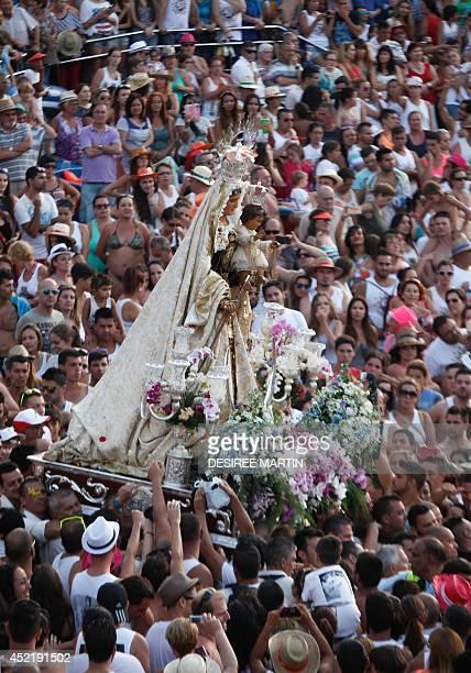 Penitents carry a statue of the Virgen del Carmen the patron saint of fishermen as thousands of people attend the procession at the Puerto de la Cruz...