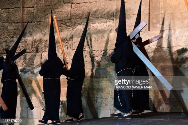 Penitents carry wooden crosses during a Holy Monday procession in Cordoba on April 15 2019 as part of the Holy Week ahead of Easter
