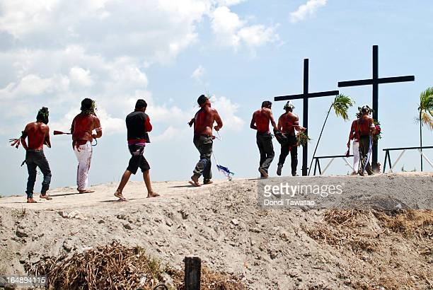 Penitents flail themselves before crosses during penitensya as a form of penance during Good Friday on March 29 2013 in Pampanga Philippines...