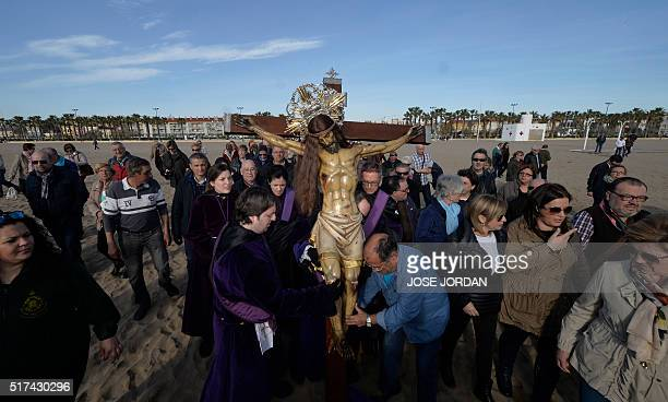 Penitents from Cristo Salvador brotherhood carry an effigy of Jesus Christ across the sand during a Holy Week procession on March 25 at the beach in...