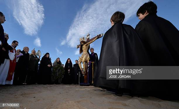 Penitents from Cristo Salvador brotherhood stand around an effigy of Jesus Christ during a Holy Week procession on March 25 at the beach in Valencia...