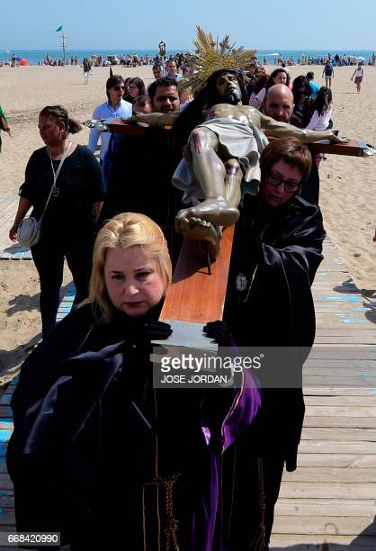 Penitents from Cristo Salvador y del Amparo brotherhood carry an effigy of a crucified Jesus Christ during a Holy week procession along the beach in...