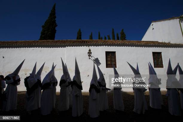 Penitents from La Paz brotherhood queue to enter Capuchinos Church before a procession during Easter Wednesday on March 28 2018 in Cordoba Spain...