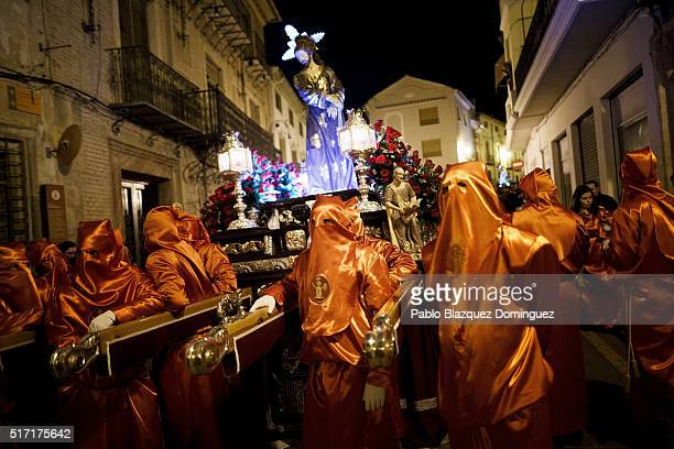 Penitents from 'Santisimo Cristo de la Misericordia' brotherhood take a break as they carry an image of Jesus at the end of a procession in the early...