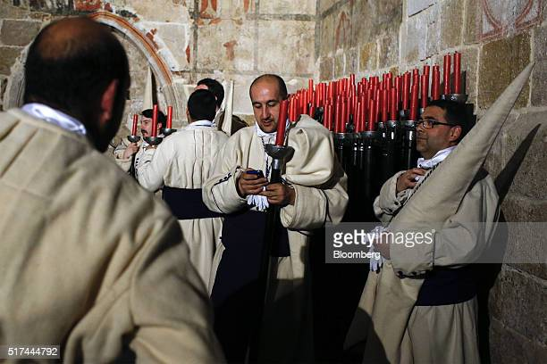 Penitents from the Brotherhood of Jesus Lying make final preparations before taking part in a procession during Holy Week celebrations in Zamora...