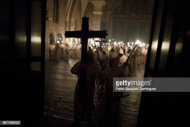 Penitents from the Cristo de la Buena Muerte brotherhood leave San Vicente church as they part in a procession in the early hours of the morning on...