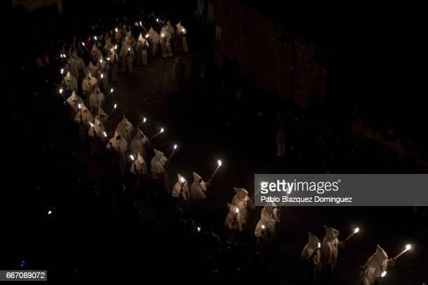 Penitents from the Cristo de la Buena Muerte brotherhood take part in a procession in the early hours of the morning on April 11 2017 in Zamora Spain...