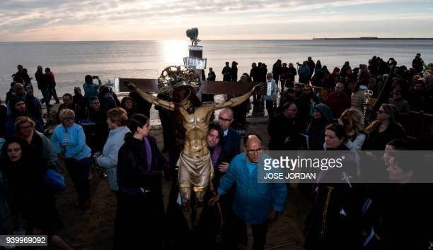 Penitents from the 'Cristo Salvador' brotherhood take part in a Good Friday procession on a beach in Valencia as part of the Holy Week on March 30...