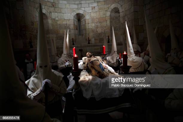 Penitents from the 'Jesus Yacente' brotherhood prepare to carry an image of 'Jesus Yacente' during a procession at Santa Maria la Nueva church on...