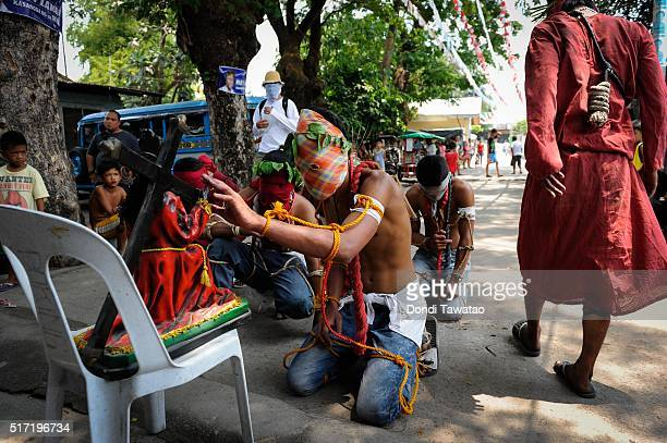 Penitents kneel and pray on March 24 2016 in Pampanga province Philippines The brutal practice is a form of reenactment of Christ's suffering before...
