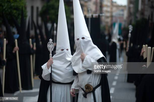 Penitents of 'Amor' brotherhood are seen chatting as they take part during the holy week procession. The Holy Week in Andalusia is one of the most...