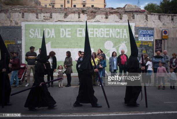 Penitents of 'Amor' brotherhood are seen walking along the street as they take part during the holy week procession. The Holy Week in Andalusia is...
