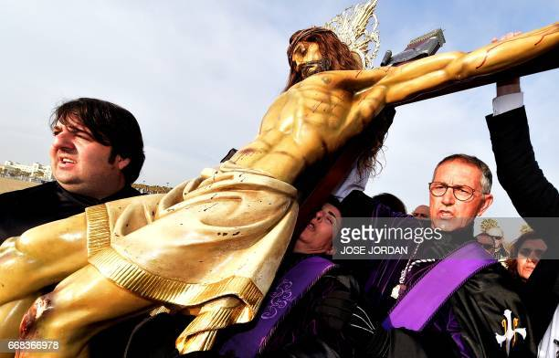 """Penitents of """"Cristo Salvador"""" brotherhood carry an effigy of Jesus Christ during a Holy week procession on April 14, 2017 at the beach in Valencia...."""