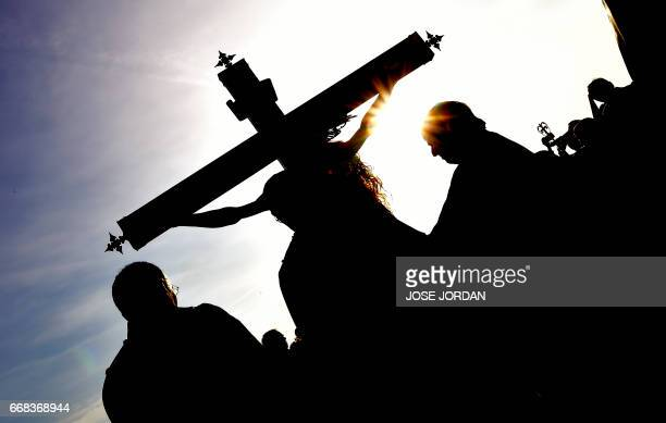 """Penitents of """"Cristo Salvador"""" brotherhood stand around an effigy of Jesus Christ during a Holy week procession on April 14,2017 at the beach in..."""
