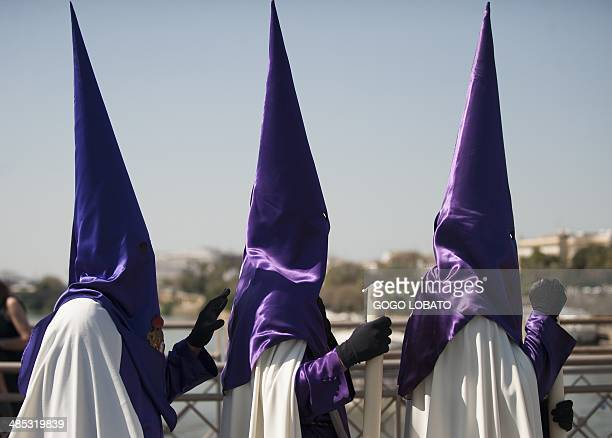 """Penitents of """"Las Cigarreras"""" brotherhood parade during a Holy Week procession in Sevilla on April 17, 2014. Christian believers around the world..."""