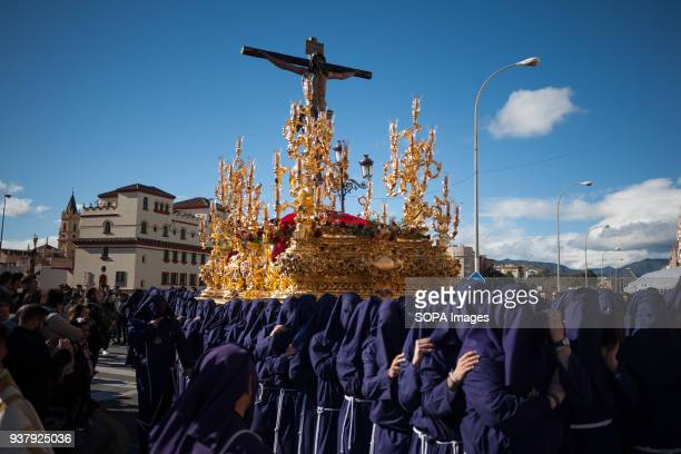 Penitents of Salud brotherhood carrying a statue of Christ as people watch the procession during the Holy Week in Malaga The Holy Week in Andalusia...