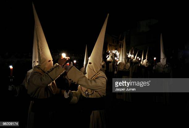 Penitents of the Hermandad de Jesus Yacente light their candles as they walk the night in silence during a Holy Week procession on April 1 2010 in...
