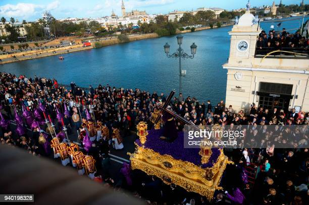 Penitents of the La O brotherhood parade over Triana bridge during a Good Friday procession as part of the Holy Week in Sevilla on March 30 2018 /...
