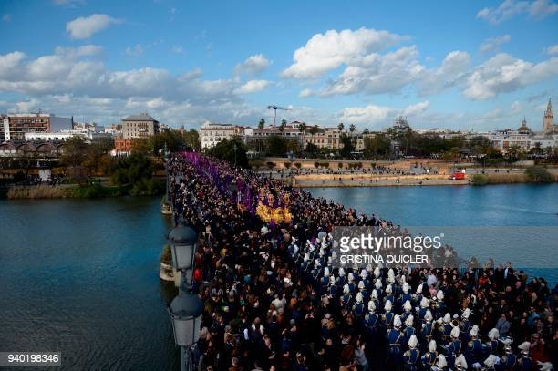 TOPSHOT Penitents of the La O brotherhood parade over Triana bridge during a Good Friday procession as part of the Holy Week in Sevilla on March 30...