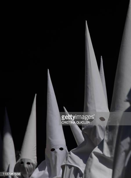 Penitents of the 'La Paz' brotherhood parade during a Palm Sunday procession in Sevilla as part of the Holy Week on April 14, 2019.