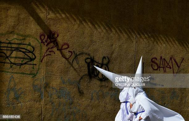 Penitents of the 'La Paz' brotherhood walk in Sevilla during the Holy Week on April 9, 2017. Christian believers around the world mark the Holy Week...