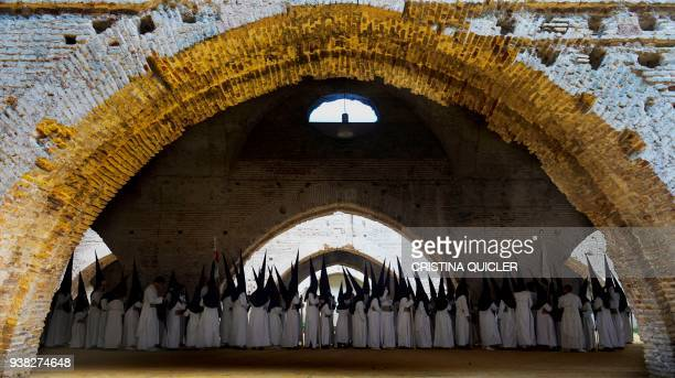 Penitents of the Las Aguas brotherhood parade at Reales Atarazanas in Sevilla during the Holy Week on March 26 2018 / AFP PHOTO / Cristina Quicler