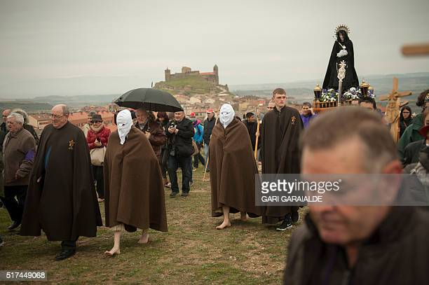 Penitents of the Santa Vera Cruz brotherhood carry a Christian effigy during the holy week procession in San Vicente de la Sonsierra in Northern...