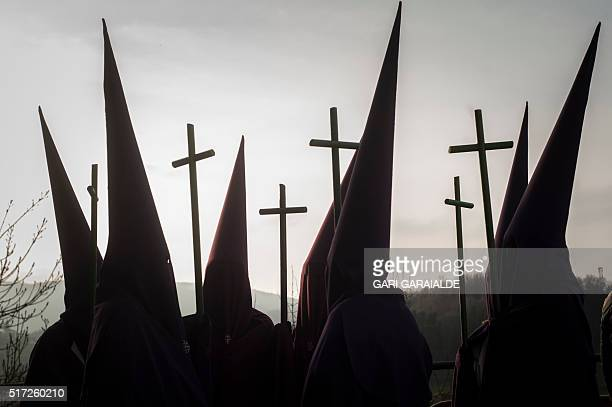 Penitents parade with crosses during a Holy Week procession in the northern Spanish Basque village of Segura on March 24, 2016. Christian believers...
