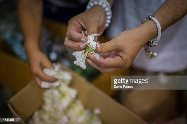 Penitents pull carnation petals out as they decorate the throne of Virgen del Carmen the day before of its festivity on July 15 2015 in Torremolinos...