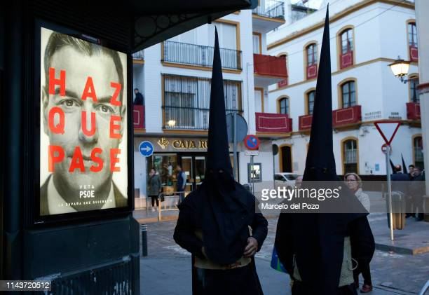 Penitents stand next to a electoral poster of Spain's Prime Minister Pedro Sanchez and Socialist Party candidate for the Spain's general election...