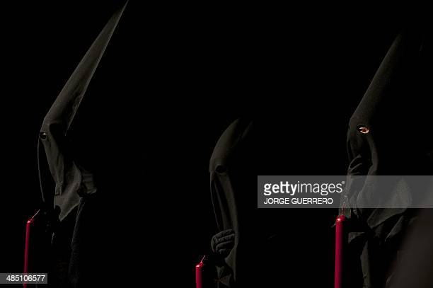 Penitents take part in the 'Fusionadas' brotherhood procession during the Holy Week in Malaga on April 16 2014 Christian believers around the world...