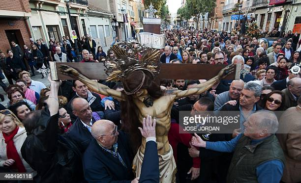 Penitents touch the effigy of Cristo Salvador during the Holy Week procession near the beach in Valencia on April 42015Christian believers around the...