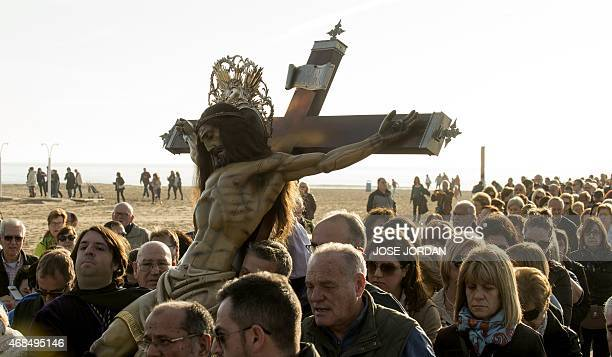 """Penitents walk beside an effigy of """"Cristo Salvador """" during the Holy Week procession on the beach in Valencia on April 4,2015.Christian believers..."""