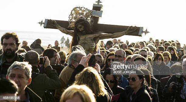 Penitents walk beside an effigy of Cristo Salvador during the Holy Week procession on the beach in Valencia on April 42015Christian believers around...