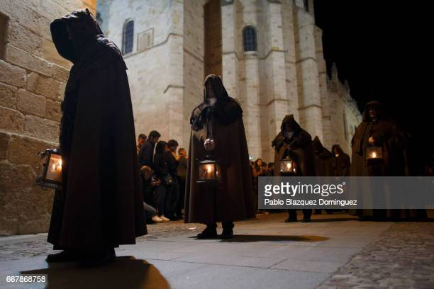 Penitents wearing brown capes from the Penitencia brotherhood take part in a procession in the early hours on April 13 2017 in Zamora Spain Spain...