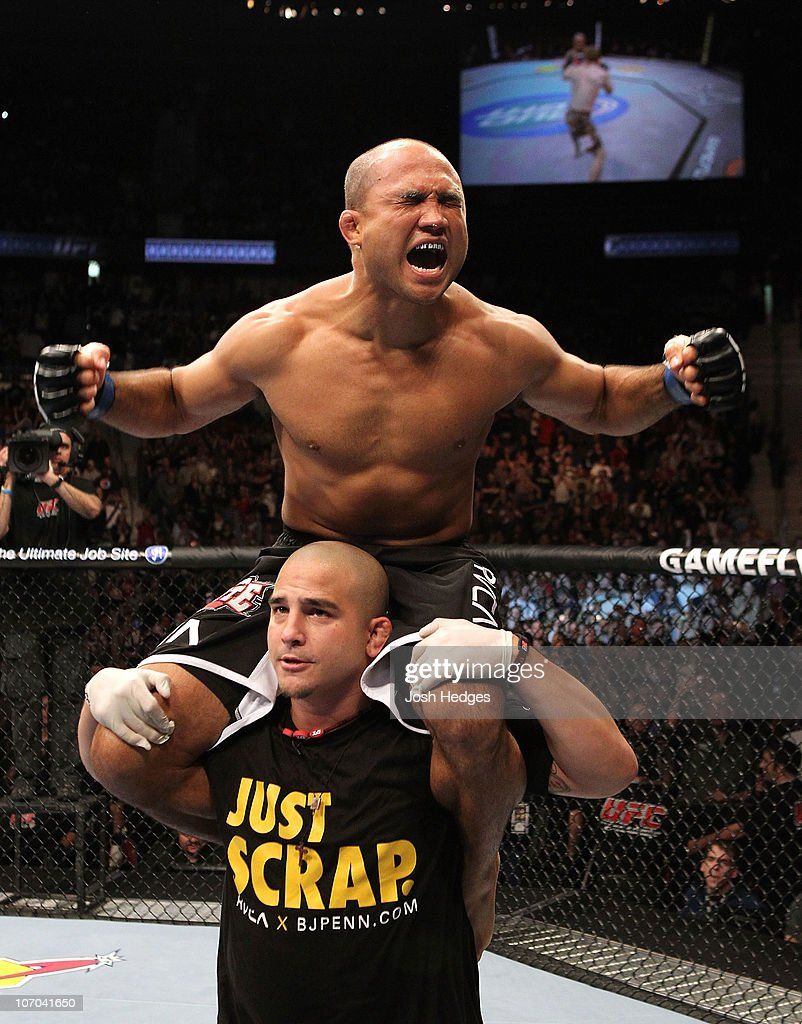 BJ Penn celebrates after he won in the first round by knockout against Matt Hughes (red gloves) during their Welterweight bout part of UFC 123 at the Palace of Auburn Hills on November 20, 2010 in Auburn Hills, Michigan.